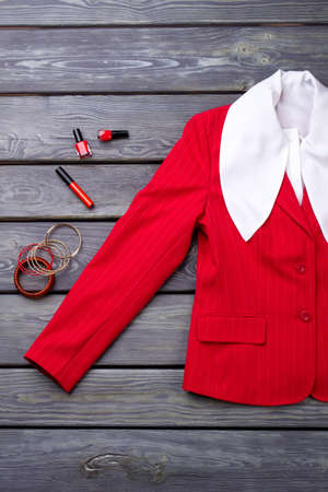 Business womans suit, flat lay. Red jacket sleeve with cosmetic accessories for makeup.