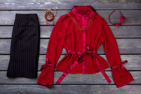 Black trousers and red blouse, flat lay. Striped pants, polyester blouse and accessories.