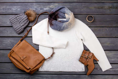 Casual winter womens clothes. Beauty feminine clothes arrangement with hat, handbag, sweater, scarf. Flat lay, top view.