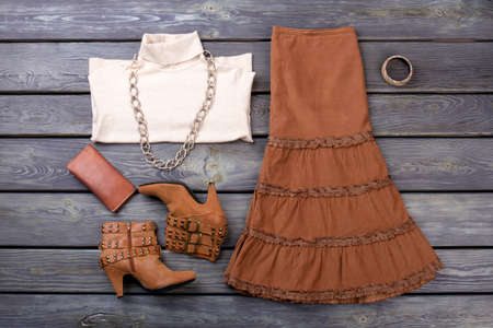 Female fashion look with stylish clothes and accessories. Wooden desk surface background.