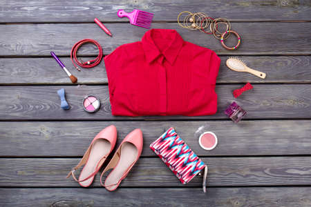 Set of professional decorative cosmetics. Folded red shirt, flat lay top view.
