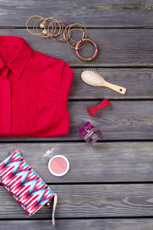 Cosmetic and make-up kit. Red folded womens shirt. Wooden desk surface background.