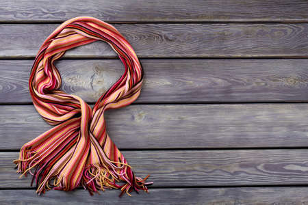 Bowed colourful wool scarf. Flat lay, top view. Black background. Stock Photo