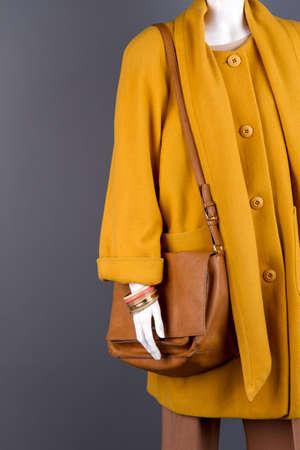 Mannequin with coat and handbag. Braceletes on dummy hand. Black background. Imagens