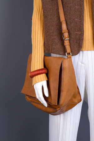 Close up brown leather handbag on mannequin. Womens winter wear, black isolated background. Imagens