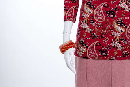 Close up braceletes on mannequin hand. Oramented red womens clothes. White isolated background.