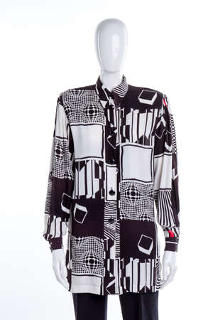 Blouse with abstract geometry print. Mannequin with shirt. White isolated background.