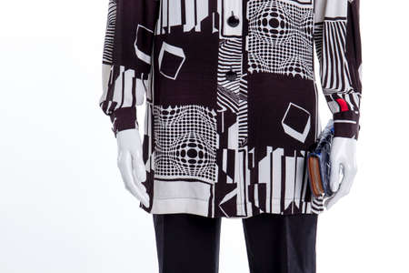Mannequin with blue purse. Black and white shirt with geometric forms.