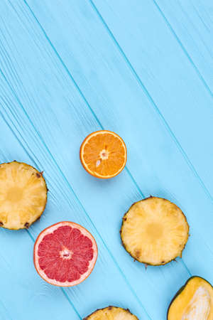 Ripe exotic fruits, top view. Blue wooden background with slices of exotic fruits and copy space. Summer healthy ingredients.