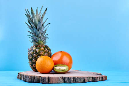 Composition of tropical fruits on natural wood. Fresh pineapple, grapefruit, orange and kiwi fruit on wooden stump. Fruits for weight loss. Stock Photo