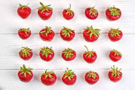 Arrangement of organic strawberries on white background. Rows of ripe juicy berries on white wooden surface. Summer fruity background.