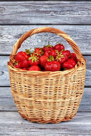 Basket of strawberries on rustic surface. Freshly picked strawberries on old wooden boards. Zdjęcie Seryjne