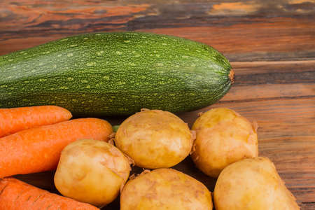 Zucchini, potatoes and carrots. Close up. Wooden desk surface background. Stock Photo
