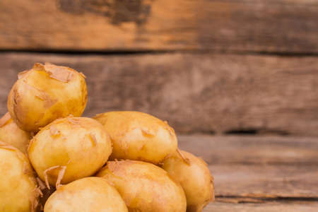 Pile of young potatoes with peel. Close up. Wooden desk background.