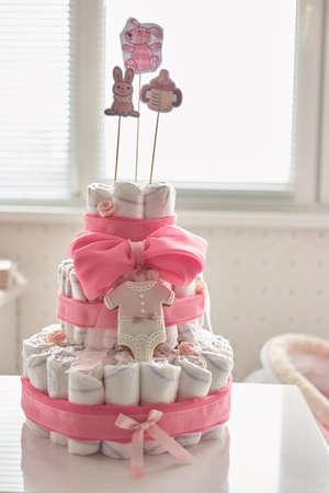 Neugeborenes Geschenkkonzept. Dekorierter Windelkuchen innen. Standard-Bild