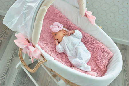 Cute newborn baby girl with hand in mouth. Lullaby moses basket. Stock Photo