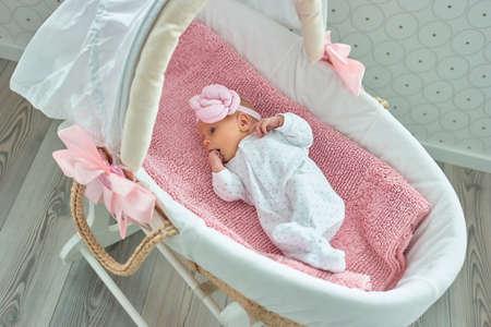 Nettes neugeborenes Baby mit Hand im Mund. Wiegenlied Moses Korb. Standard-Bild