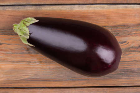 Ripe fresh eggplant close up. Healthy fresh eggplant shot on wooden background.