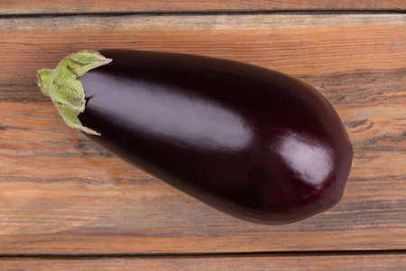 Ripe fresh eggplant close up. Healthy fresh eggplant shot on wooden background.
