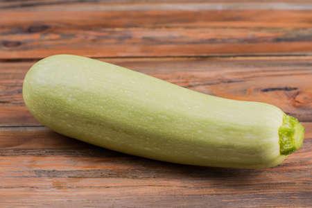 Organic raw fresh zucchini. Close up. Big green courgette on wood.
