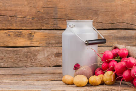 Enamelware milk churn and vegetables. Potatoes, radishes and beetroot on wooden background.