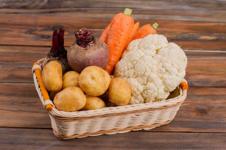 Fresh vegetables in wicked basket. Wooden desk table background.