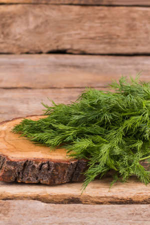 Green dill and wooden cut board. Cooking salad. Wooden rustic table background.
