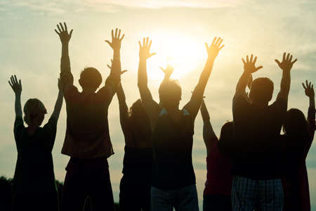 People raising hands up, rear view. Morning sunshine background. Imagens
