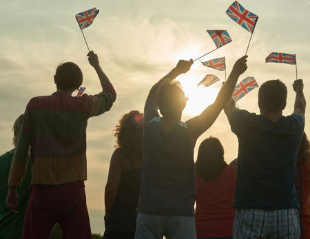 Back view, silhouette of british people with flags. Patriotic british family, rear view. Stock Photo