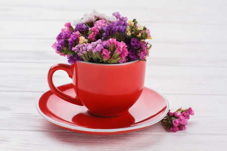 Bouquet of beautiful statice little flowers in a red mug. White wooden table background.