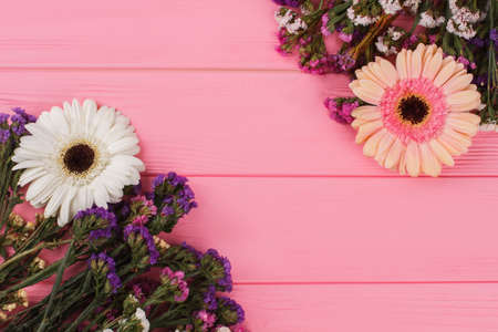 Statice and daisy flowers. Pink wooden background.