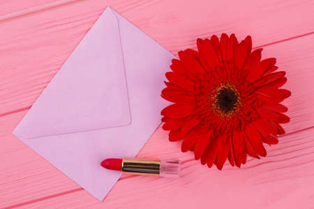Female belongings and envelope. Post mail, red lipstic and red daisy flower. Pink wooden table background. Stock Photo