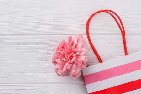 Carnation flower and striped shopping bag. White wood background. Copyspace.