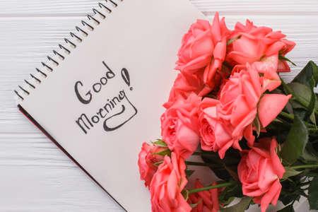 Flores color de rosa y deseo de buenos días en el bloc de notas. De cerca. Fondo de madera blanca.