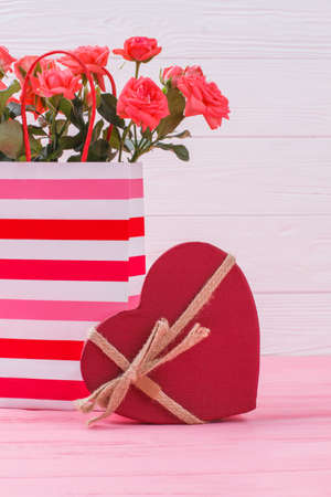 Bouquet of red flowers and red gift box. Pink wooden background. Stok Fotoğraf