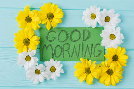 Good morning note and golden-daisy flowers composition. Top view, flat lay. Blue wood background.