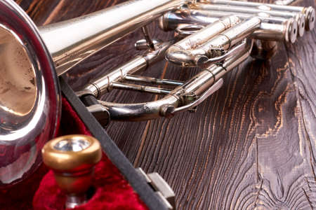 Old trumpet on textured wooden background. Rusty trumpet on brown wooden surface. Classical music instrument.