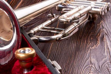trompeta vieja en el fondo con textura de madera . trompeta oxidada en la madera marrón. mármol clásico de la música Foto de archivo
