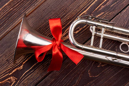 Trumpet with red bow. Shiny trumpet with red bow on brown wooden background. Instrument of jazz music.