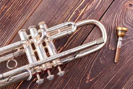 Silver trumpet on brown wooden background. Musical trumpet with clipping path. Classical musical instrument. 写真素材