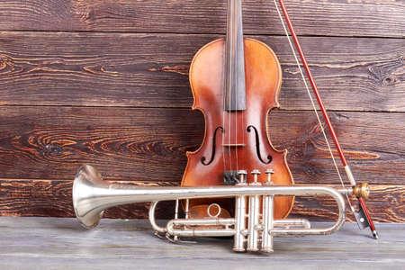 trompeta y violín en el fondo de madera. instrumentos musicales de navidad en superficie marrón de madera .