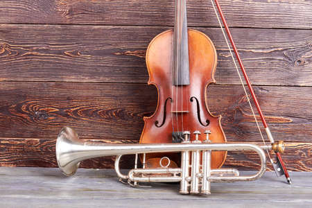 Trumpet and violin on wooden background. Vintage musical instruments on brown wooden surface. Foto de archivo