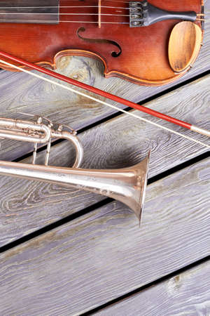 Antique violin and trumpet on wooden floor. Artistic musical instruments and copy space. Create your music.