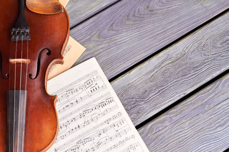 Violin on old wooden boards. Sheets of musical notes and violin on wooden surface with text space. Stringed instrument of classical music.