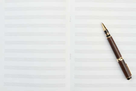 Pen on musical notes and copy space. Top view on blank notebook for musical notes and ballpoint pen, vertical image. Musical education accessories. Stock Photo