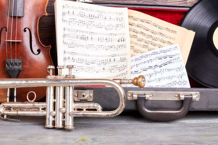 Vintage musical instruments background. Old trumpet, violin, musical notes and vinyl record close up. Retro music style. Archivio Fotografico