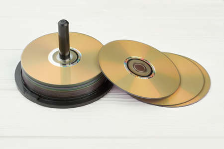 Stack of compact discs on white background. Group of blank disks on wooden surface. Digital storage of information.