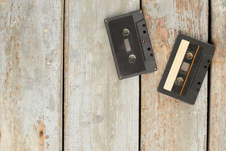 Used audio cassettes on old wooden floor. Two vintage cassette tapes on wooden planks and copy space. Retro music devices.