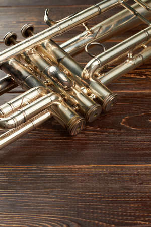 Detail of old trumpet instrument. Close up trumpet on wooden background with copy space. Classical orchestral instrument.