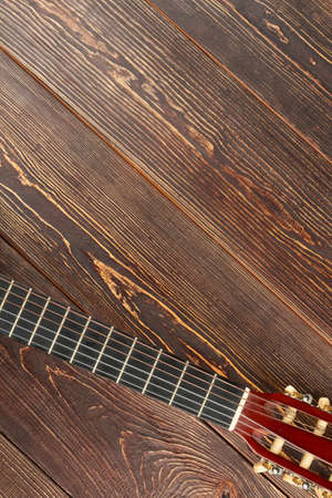 Acoustic classic guitar head and copy space. Fretboard of six-strings guitar on textured wood with text space.